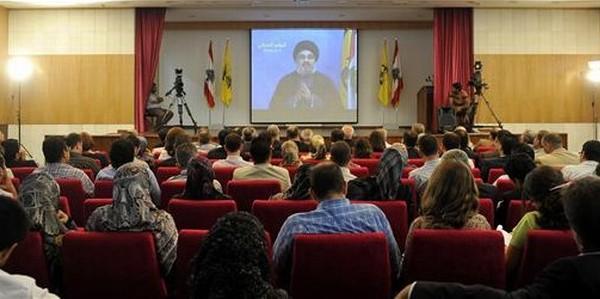 Varias personas siguen desde Beirut el discurso de Hassan Nasrallah, líder de Hizbulá.