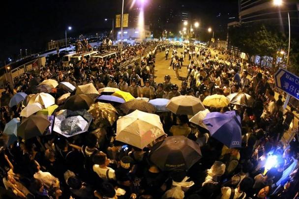 Los manifestantes, protegidos con paraguas de los gases, se enfrentan con la Policía de Hong Kong. (Facebook Occupy Central)