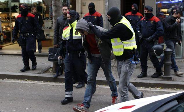 Mossos d'Esquadra escoltan a un detenido en la calle Gran de Sant Andreu durante la operación antiterrorista para desarticular una organización anarquista a la que se atribuyen diversos atentados con artefactos explosivos. / Alejandro García (Efe).