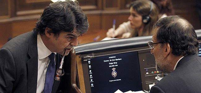 Moragas, al alto cargo mejor pagado del Gobierno, junto al presidente Rajoy en el Congreso. / Efe