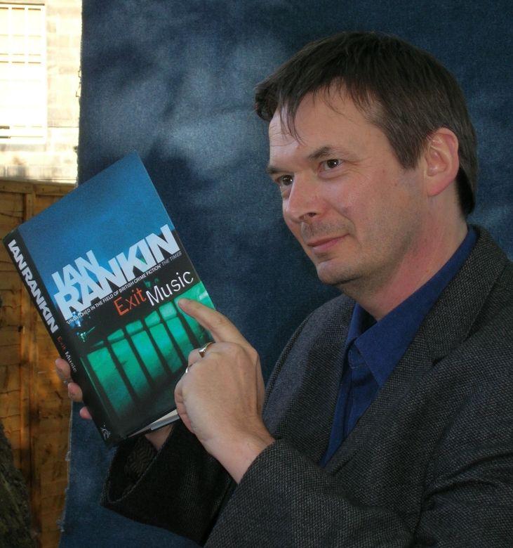 Ian Rankin sosteniendo un ejemplar de la serie de Rebus, Exit Music, traducido al español como 'La música del adiós'. / Wikipedia