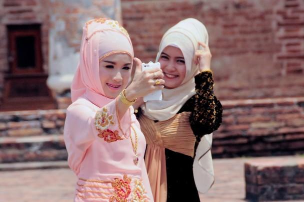 Dos jóvenes se toman autorretratos con el móvil frente a la mezquita de Krue Se. / M. G. P.