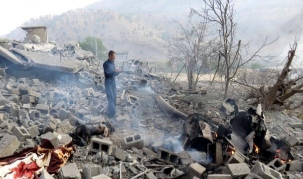 Estado en que quedó la aldea de Zergele (norte de Irak). Junto al hombre se aprecia una de las víctimas del bombardeo turco. / Firat News