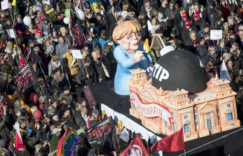 Una de las carrozas de la protesta, con Angela Merkel a punto de prender la mecha del TTIP. / Kay Nietfeld (Efe)