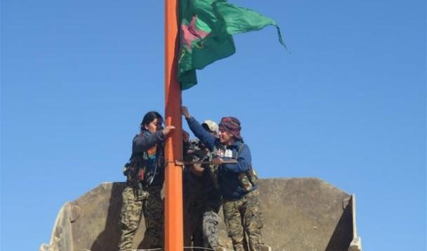 Varias jóvenes de las YPJ colocan su bandera tras haber arriado las del Estado Islámico en Tal Sinam, al norte de Raqqa (Siria). / Hawar News