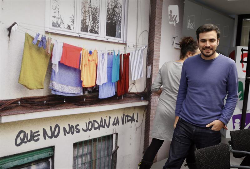 Alberto Garzón, ante el cartel de la campaña 'Que no nos jodan la vida'.