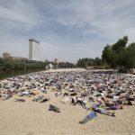 Un momento de la 'performance' para recordar a los refugiados ahogados, realizada en la playa de las Moreras, en Valladolid.
