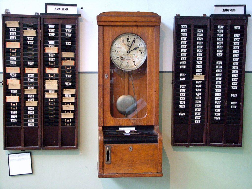 Una antigua máquina de fichado de entrada y salida del trabajo, para control de los empleados, con sus casilleros para las tarjetas