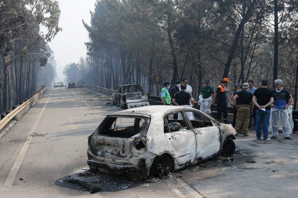 Bomberos, agentes de policía y Protección Civil, y personal forense hacen un alto en el trabajo junto a dos de los vehículos quie ardieron cuando las llamas envolvieron de golpe la carretera.