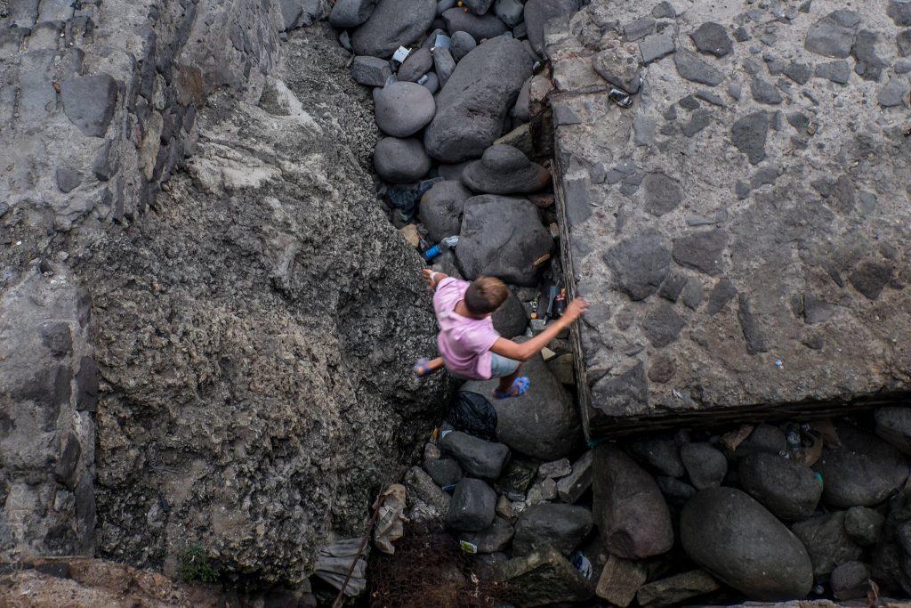 Un niño arriesga la vida al saltar entre las rocas del puerto en Melilla