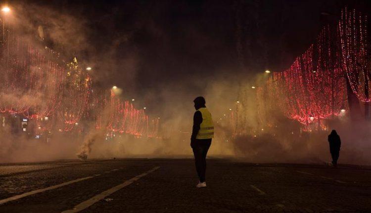 Un manifestante de chaleco amarillo está parado en medio del humo durante una manifestación en París, Francia, el 8 de diciembre. / EFE